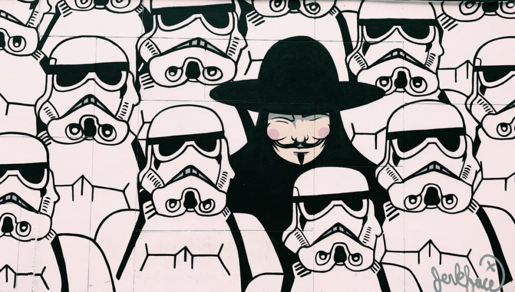 Graffiti art of stormtroopers and one person in a Guy Fawkes mask.
